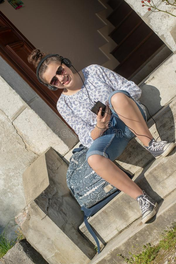 Smiling young teen girl sitting on the steps, listening a music stock image