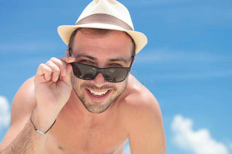 Smiling young topless man takes off his sunglasses stock image