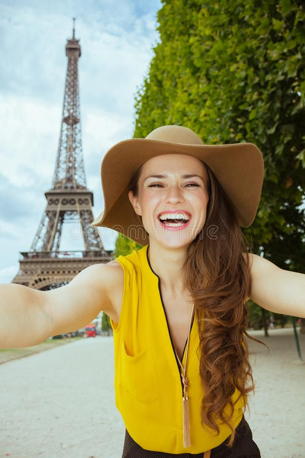 Tourist woman against clear view of Eiffel Tower taking selfie stock photo