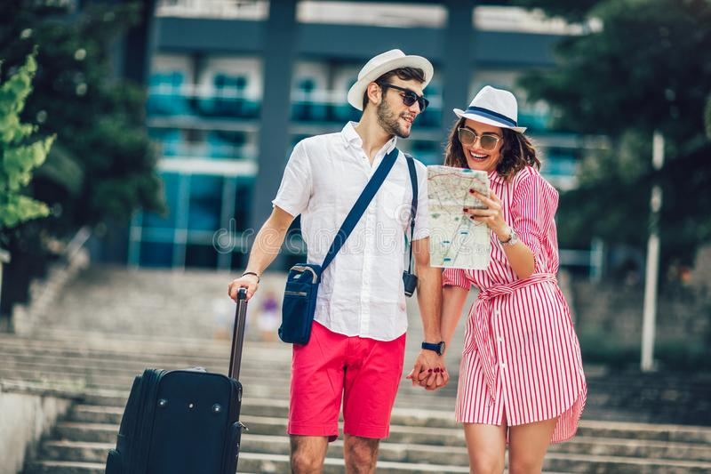 Young travellers couple reading city map and looking for hotel stock images