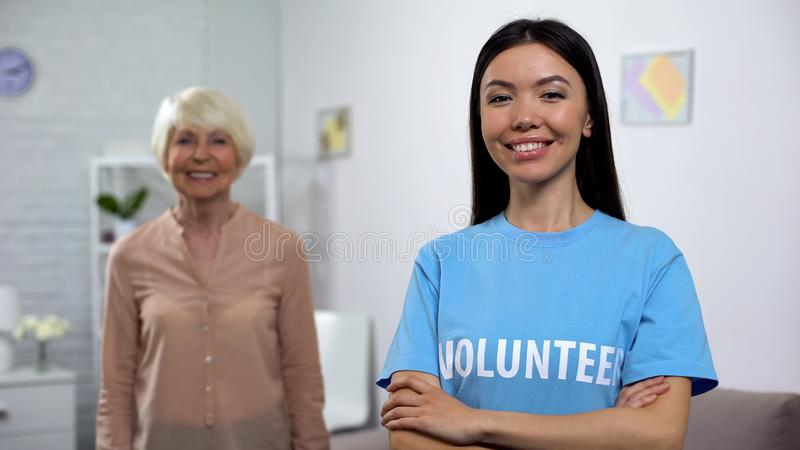 Smiling young volunteer with happy old lady on background, social protection royalty free stock photos