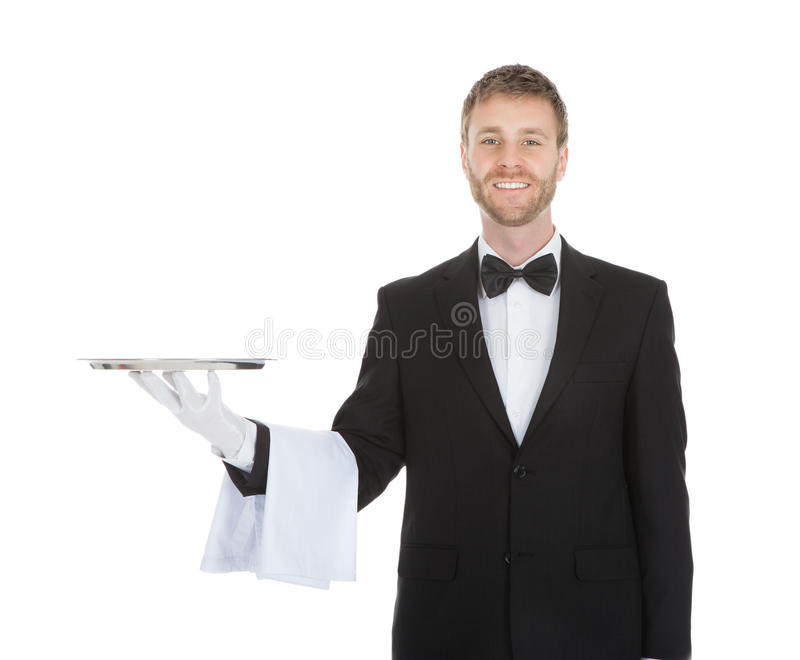 Smiling young waiter holding empty serving tray. Portrait of smiling young waiter holding empty serving tray isolated over white background royalty free stock images