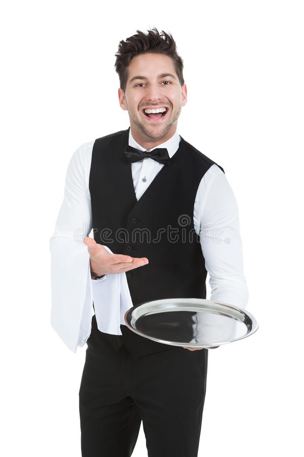 Smiling young waiter holding empty serving tray. Portrait of smiling young waiter holding empty serving tray isolated over white background stock photo