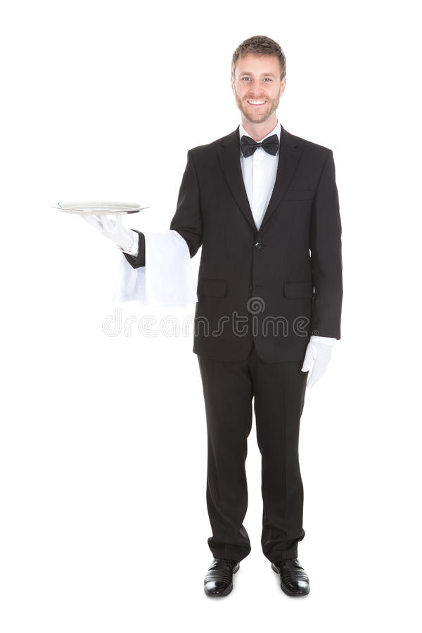 Smiling young waiter holding empty serving tray. Portrait of smiling young waiter holding empty serving tray isolated over white background royalty free stock image
