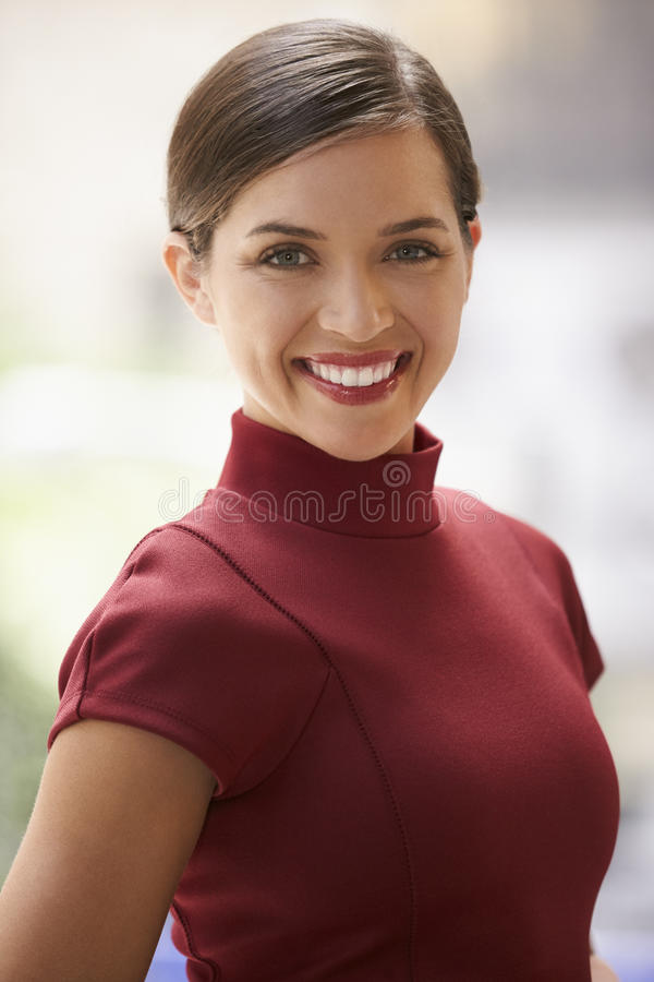 Smiling young white businesswoman in maroon dress, vertical royalty free stock photos