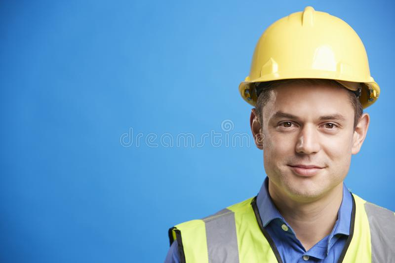 Smiling young white construction worker in hard hat stock images