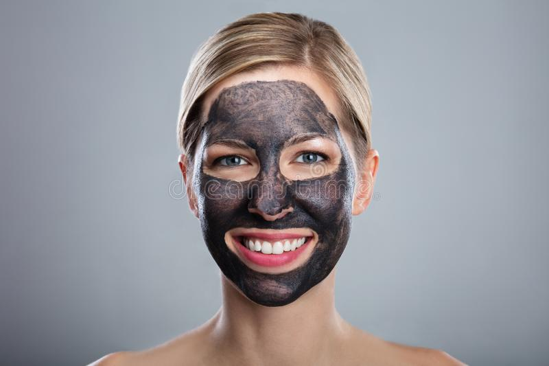 Smiling Young Woman With Activated Charcoal Face Mask stock images