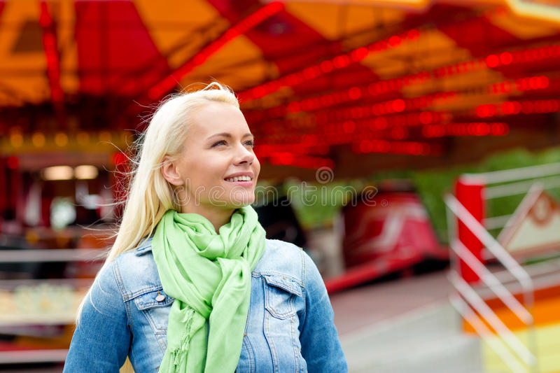 Smiling young woman in amusement park. Leisure, amusement park and people concept - smiling young woman in amusement park with carousel on the back royalty free stock images