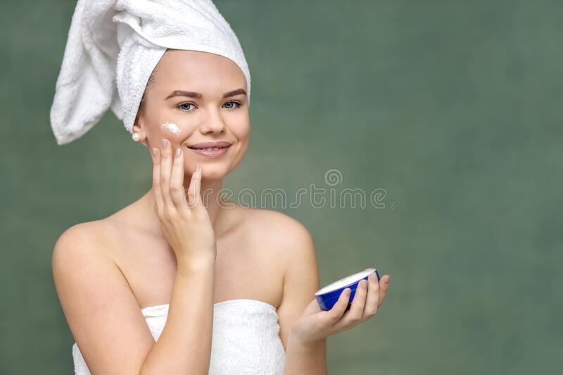 Smiling young woman applying moisturizer on face for healthy skin stock photo