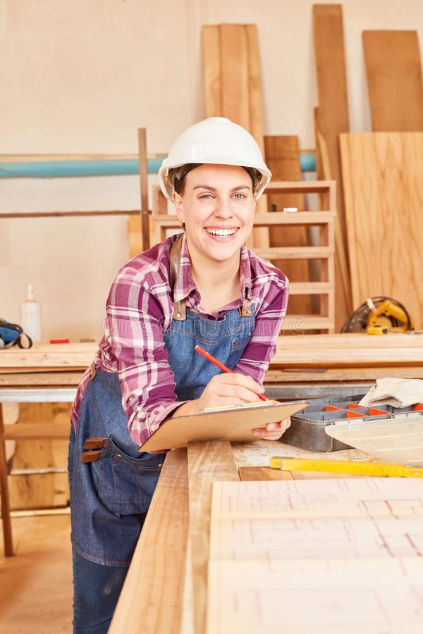 Smiling young woman as a craftsman apprentice royalty free stock photos
