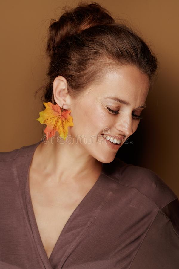 Smiling young woman with autumn leaf earring isolated on beige royalty free stock image