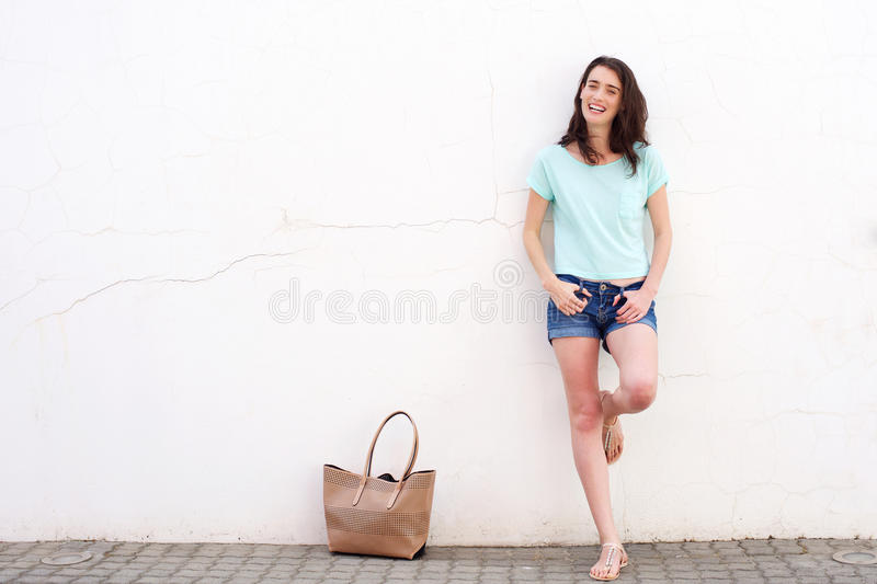 Smiling young woman with bag leaning against white wall stock photo