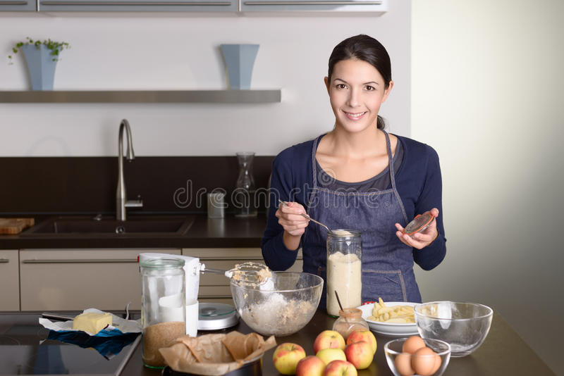 Smiling young woman baking an apple tart royalty free stock photos