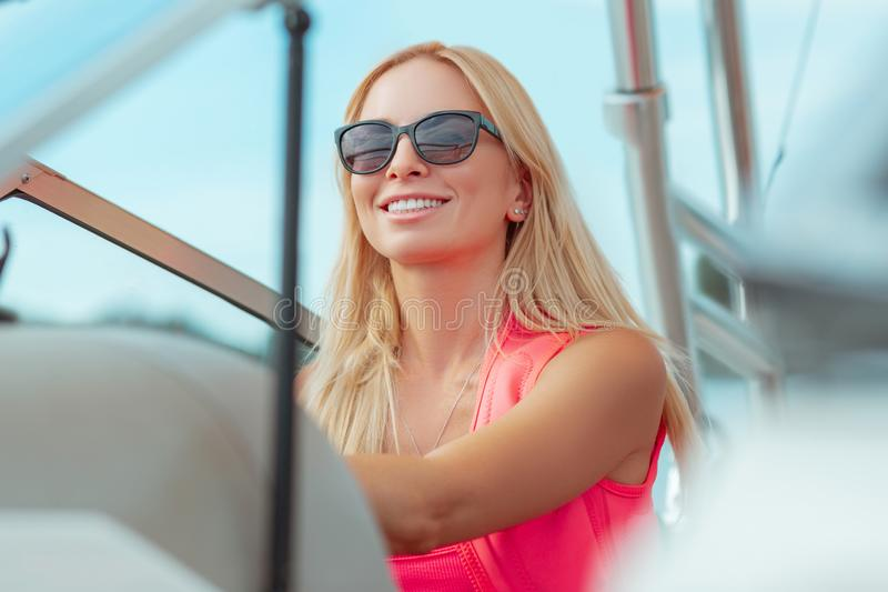 Smiling young woman with blonde hair wearing sunglasses stock photos