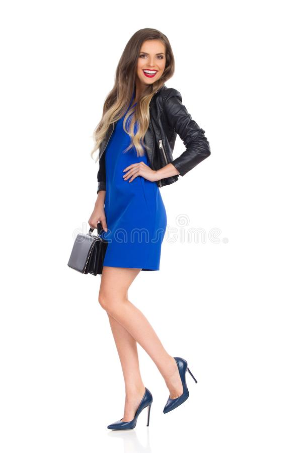 Smiling Young Woman In Blue Mini Dress And Leather Jacket Is Standing On One Leg With Black Bag stock images