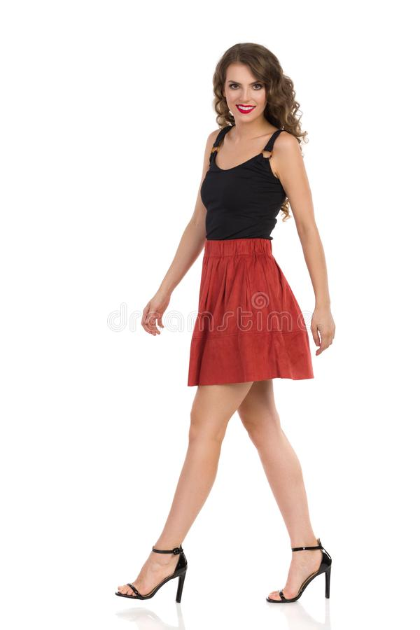 Young Woman In Brown Suede Mini Skirt And High Heels Is Walking And Looking At Camera. Side View. Smiling young woman in brown suede mini skirt, black top and stock images
