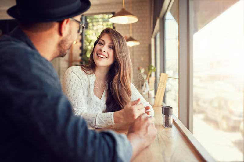 Smiling young woman at cafe with her boyfriend stock images