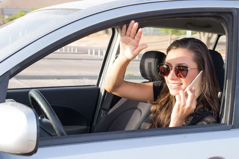 A young woman in the car talks on the smart phone and drives stock photo
