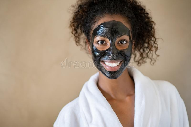 Smiling woman with charcoal face mud. Smiling young woman with charcoal face mud looking at camera  on beige background with copy space. Portrait of african royalty free stock photography
