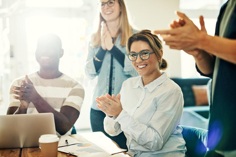 Smiling young woman clapping with colleagues in a modern office royalty free stock image