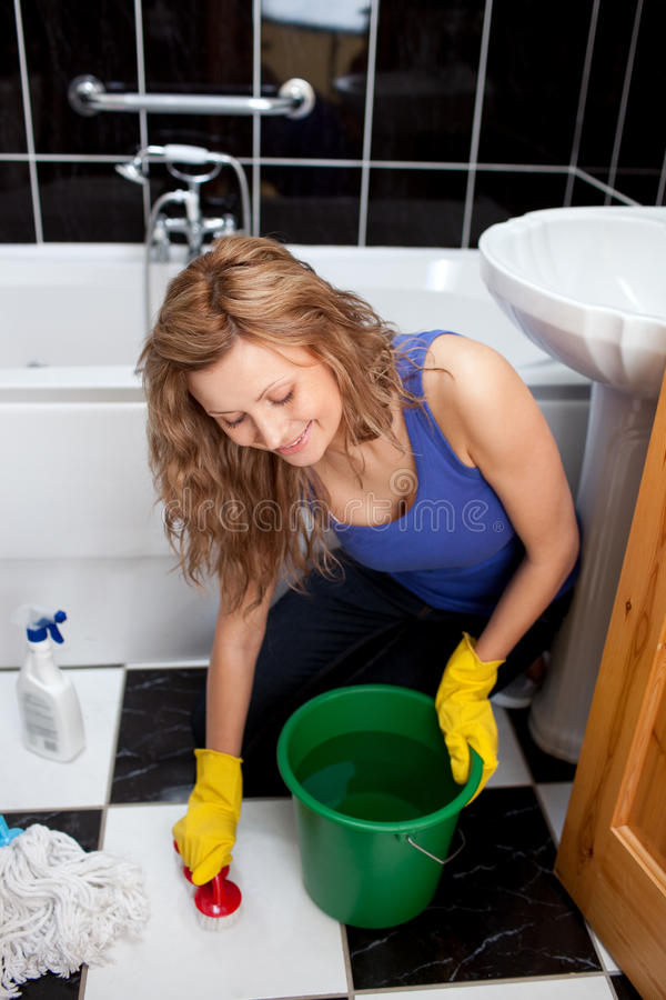 Smiling young woman cleaning bathroom s floor