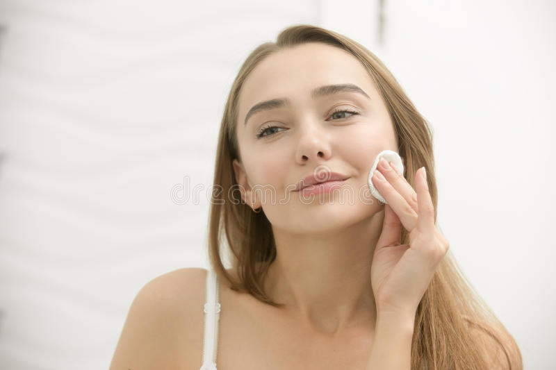 Smiling young woman cleaning her skin with a cotton pad,. Looking at the mirror at home bathroom. Beauty, skin care concept, lifestyle royalty free stock photography