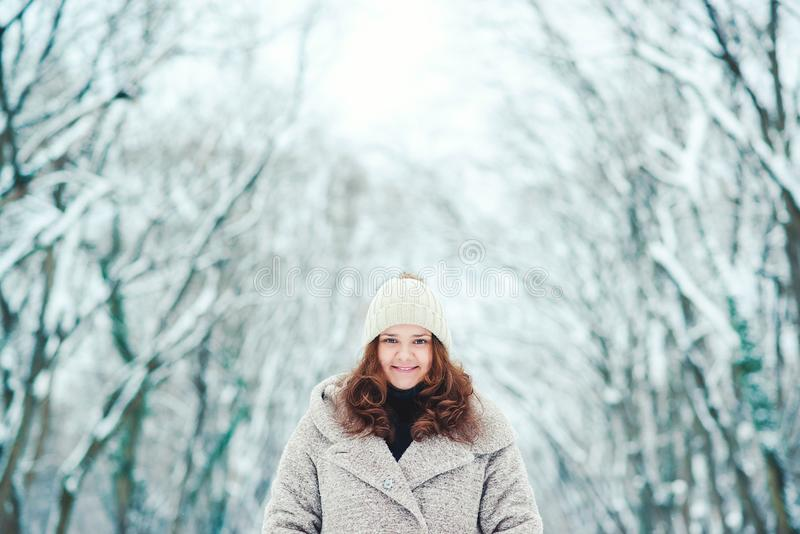 Smiling young woman in coat walking at winter park. Expressing girl with positive emotions, christmas mood, amazing smile, winter stock photography