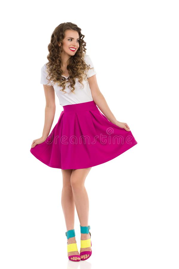 Smiling Young Woman In Colorful High Heels, Pink Mini Skirt And White Top. Beautiful young woman in colorful high heels, pink mini skirt and white top is royalty free stock image