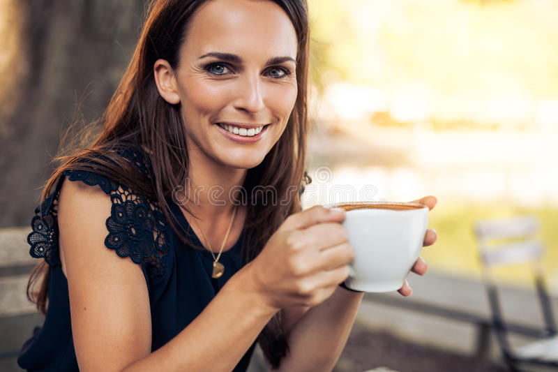 Smiling young woman with a cup of coffee stock image