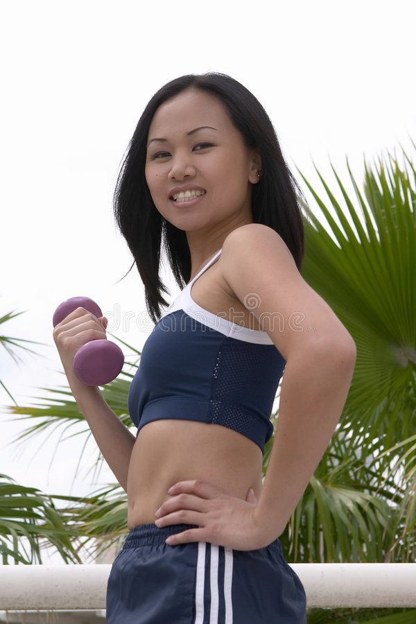 Smiling Young Woman Curling Dumbbell royalty free stock photo