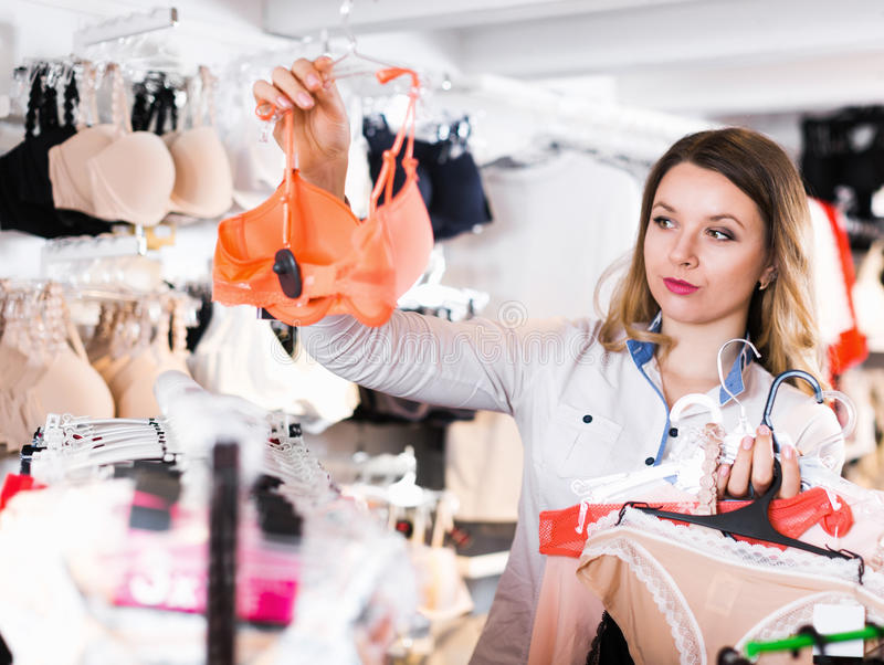 Smiling young woman customer choosing lingerie royalty free stock photos