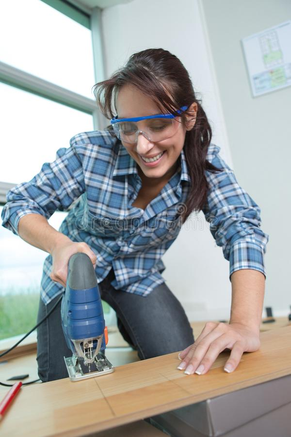 Smiling young woman cutting wooden plank stock photo