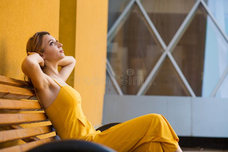 Smiling young woman day dreaming about vacation looking up stock image