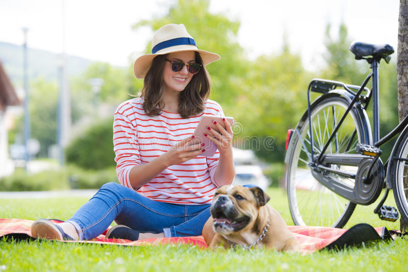 Smiling young woman with digital tablet outdoor royalty free stock photos