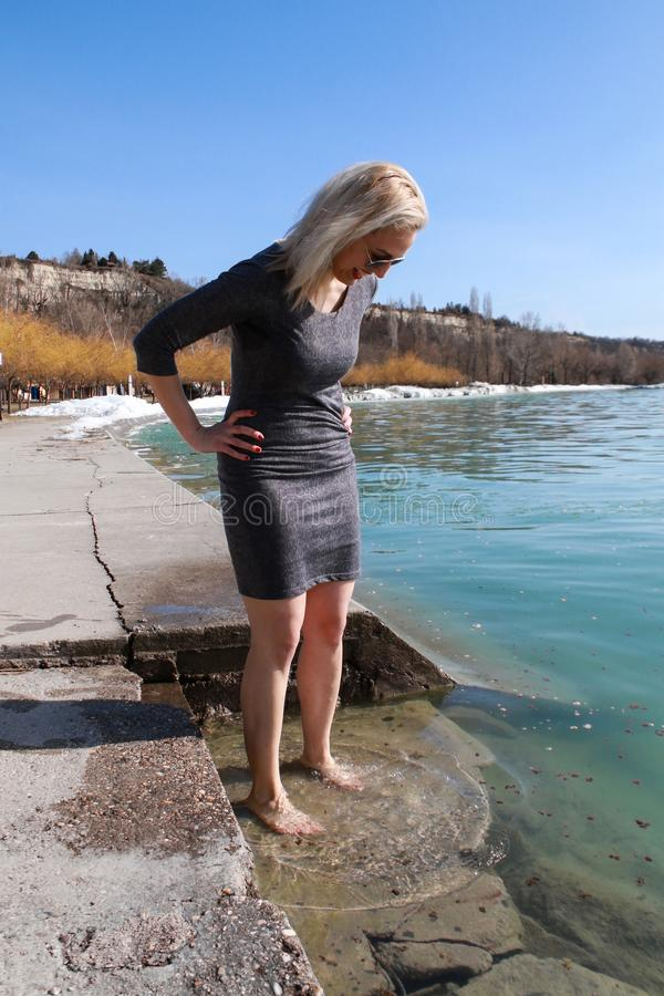 Smiling young woman is dipping her feet in the frozen water of lake. Smilyng youn woman is dipping her feet in the frozen wter of hungarian lake balaton royalty free stock images