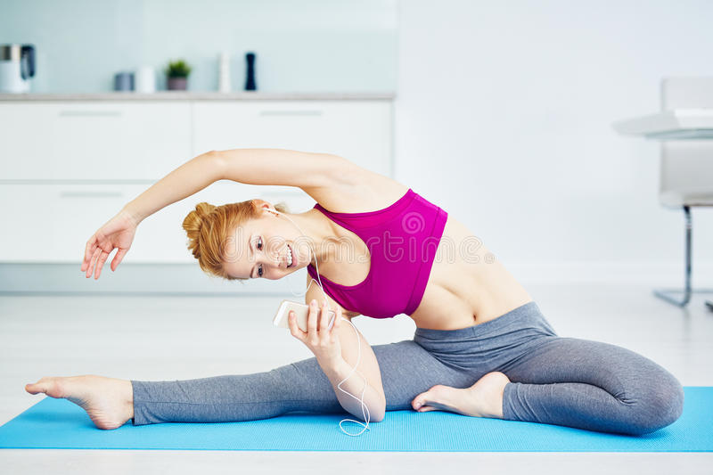Smiling Young Woman Doing Stretching Exercises royalty free stock photography