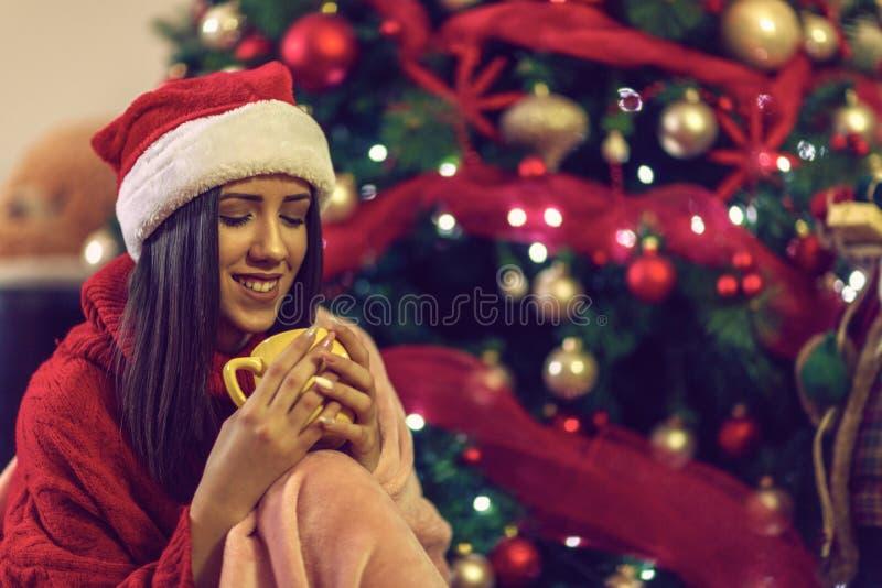 Smiling woman drinking from tea mug at Christmas eve royalty free stock image