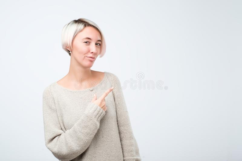 Smiling young woman with dyed short hair pointing finger away stock image