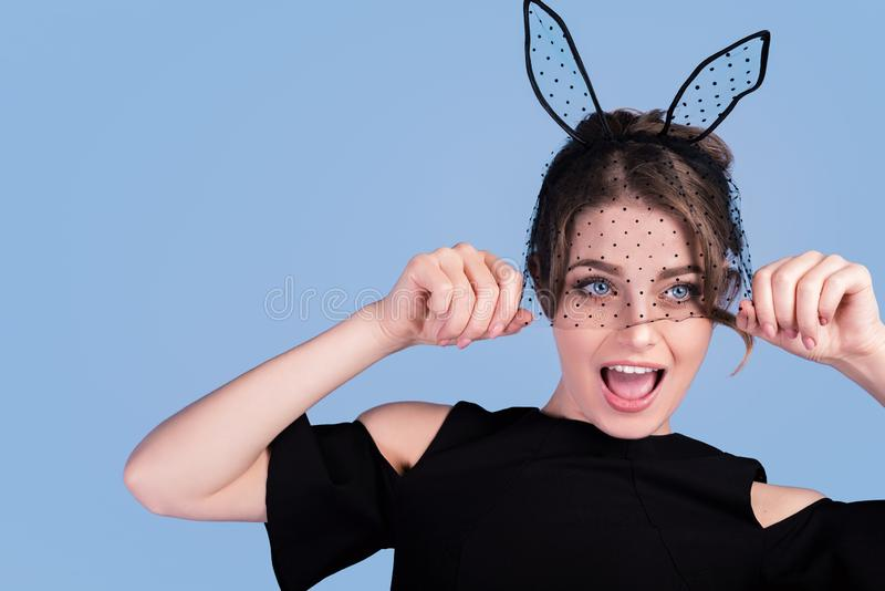 Smiling young woman in Easter bunny ears isolated on blue background copy space royalty free stock photos