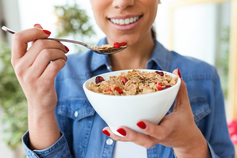 Smiling young woman eating breakfast cereals of bowl at home royalty free stock images