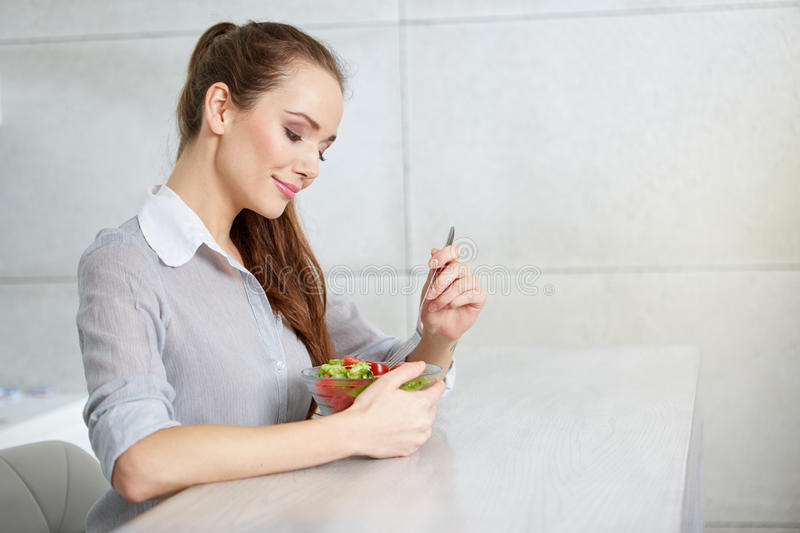 Smiling young woman eating fresh salad in modern kitchen royalty free stock image