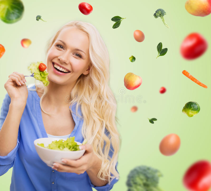 Smiling young woman eating green vegetable salad stock image