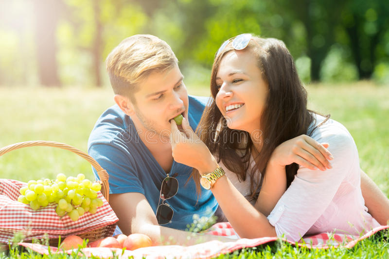Smiling Woman Feeding Grape To Her Boyfriend. Smiling Young Woman Feeding Grape To Her Boyfriend In Park stock images