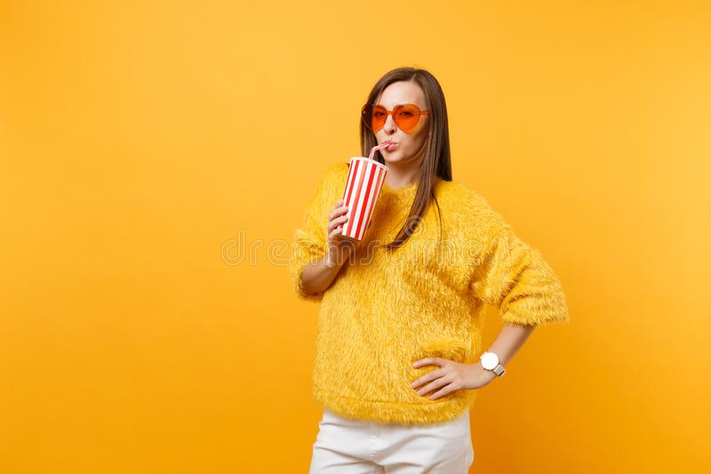 Smiling young woman in fur sweater and heart orange glasses drinking cola or soda from plastic cup isolated on bright. Yellow background. People sincere royalty free stock photography