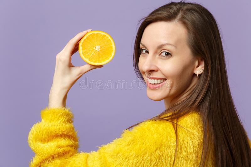 Smiling young woman in fur sweater holding in hand half of fresh ripe orange fruit isolated on violet pastel background. In studio. People vivid lifestyle stock image