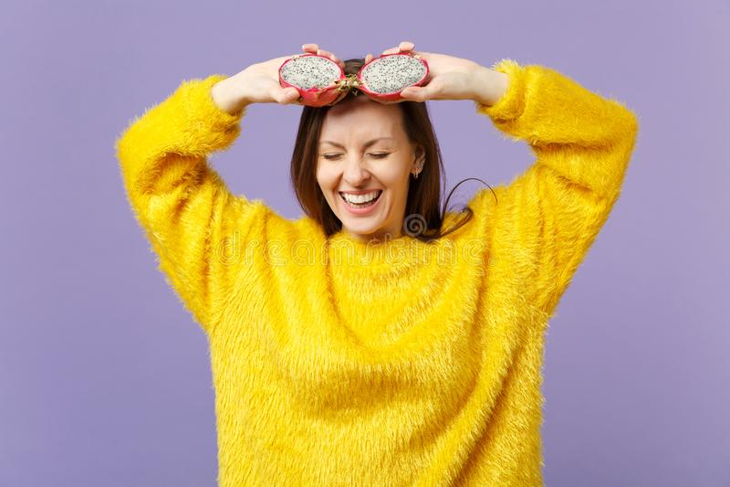 Smiling young woman in fur sweater keeping eyes closed holding halfs of pitahaya, dragon fruit isolated on violet pastel royalty free stock photography