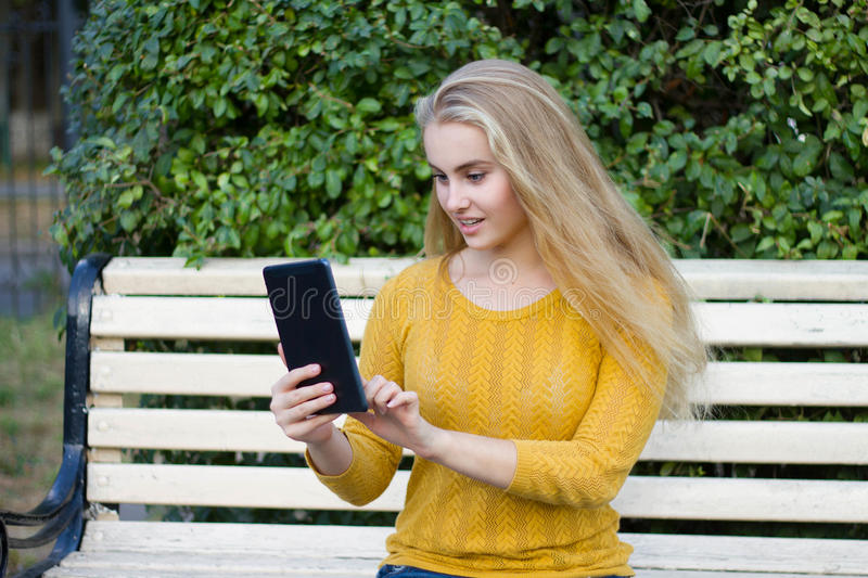 Smiling young woman or girl with a tablet computer outdoors royalty free stock image