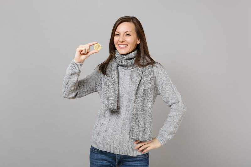 Smiling young woman in gray sweater, scarf hold bitcoin, future currency isolated on grey wall background. Healthy stock photos