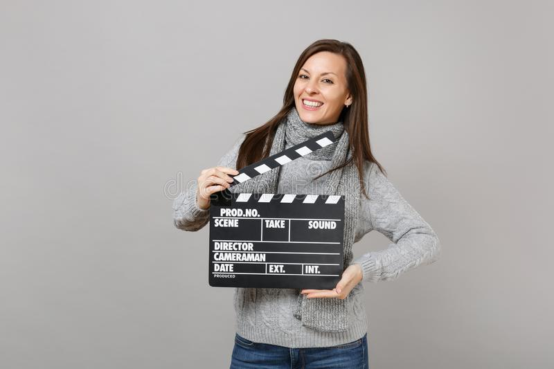 Smiling young woman in gray sweater, scarf hold classic black film making clapperboard isolated on grey background stock photography
