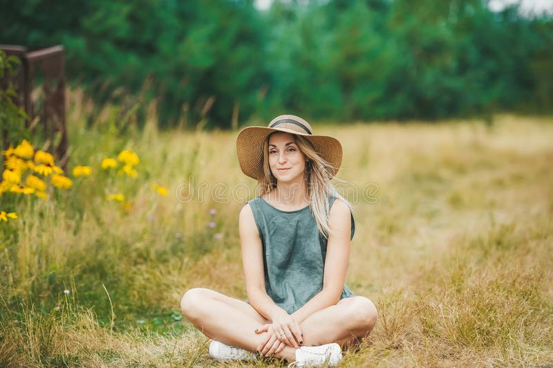 Smiling young woman in hat sit in lotus pose at summer meadow royalty free stock image